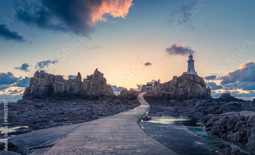 Photo Road to La Corbiere lighthouse on the sea bottom in a low tide with cliff and su