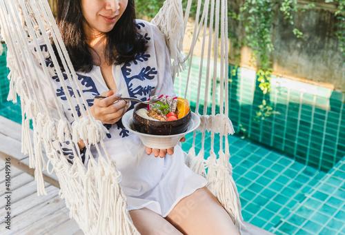фотография Woman holding bowl of smoothy sitting on hammock by swimming pool