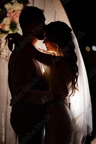 Canvas Print silhouette of the newlyweds in the dark. shooting at night.