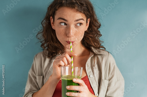 Valokuva Young woman drinking detox juice with straw on blue wall