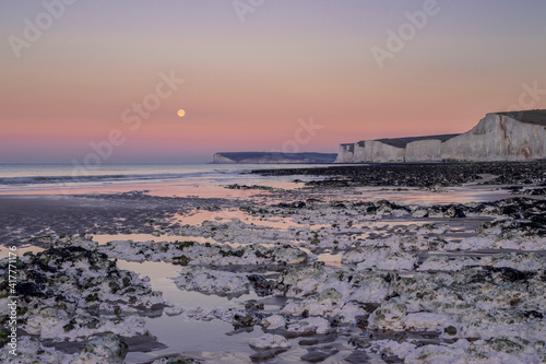 Wallpaper Mural Full snow February moon setting over the east Sussex coast at low tide in south
