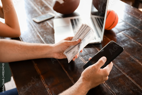Canvas Young man with money and mobile phone placing sports bet