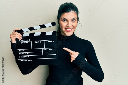Canvas Print Young hispanic woman holding video film clapboard smiling happy pointing with ha