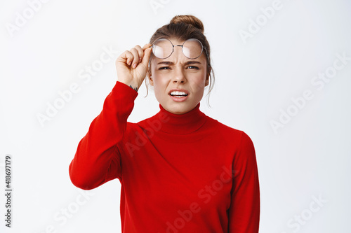 Wallpaper Mural Image of confused blond girl take-off glasses and squinting, trying to see somet