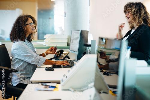 Fényképezés Friendly receptionist helping a woman.
