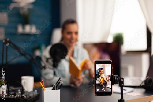 Fototapeta Vlogger holding book during podcast review on social media