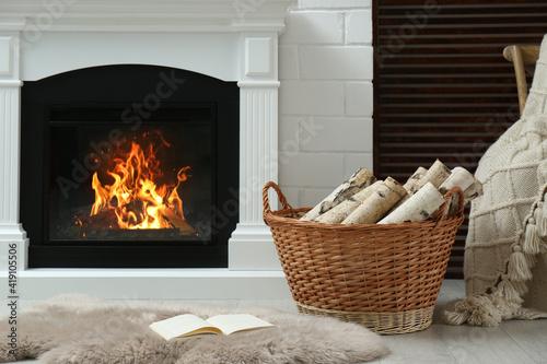 Canvas Print Firewood in wicker basket near fireplace indoors