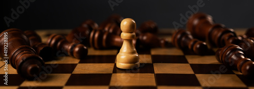 Fotografiet One white pawn is winner among fallen black chess pieces on chessboard