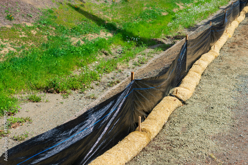 Obraz na plátně Straw wattles and plastic fence placed along dry creek to reduce soil erosion, debris runoff and retain sediment during construction and maintenance project