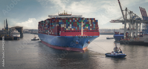 Fotografie, Obraz Container terminal in the port of Hamburg with large container ship and tugs