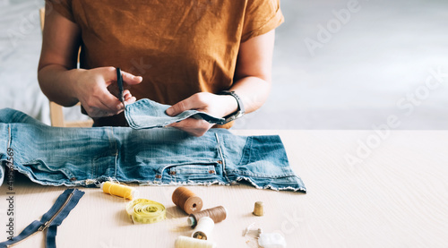 Fotografering Woman repairs sews reuses fabric from old denim clothes economical reuse