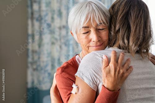 Canvastavla Senior woman embracing daughter after covid immunization vaccine