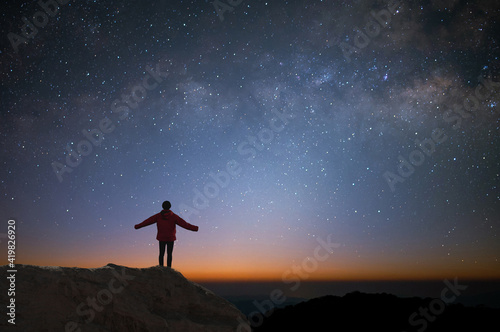 Fotografia Silhouette of young traveler and backpacker watched the star and milky way alone on top of the mountain