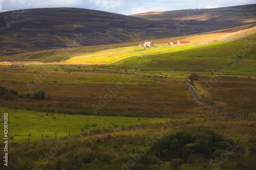 Obraz na plátne Dramatic dappled light over rural countryside landscape and old farmhouse in the Cairngorms National Park, Scottish Highlands, Scotland