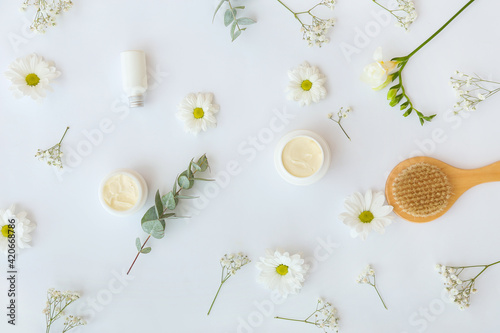 Fotografia Composition with cosmetic products, hair comb and beautiful flowers on light bac