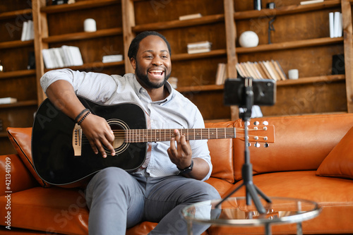 Photo Proffesional hispanic black man on the soft comfortable couch with guitar at mob