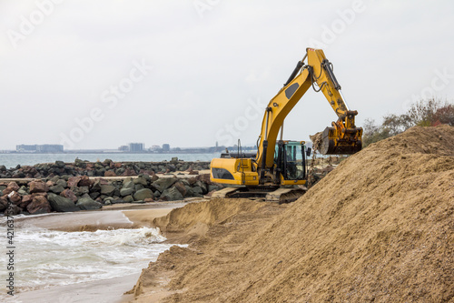 Canvas-taulu An excavator makes a mound of sand on the seashore