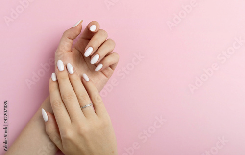 Stampa su Tela Hands of a beautiful well-groomed woman with feminine nails on a pink background
