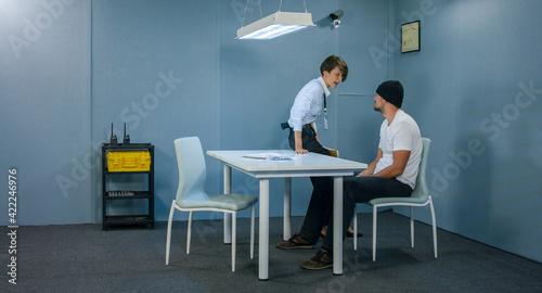 Obraz na płótnie Angry detective woman in interrogation room screams at suspect.
