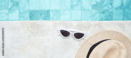 Fotografia white sunglasses and hat near swimming pool in luxury hotel