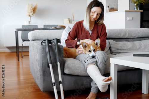 Fotografia Adult woman in her late twenties on couch at home with crutches and orthopedic plaster caress the dog
