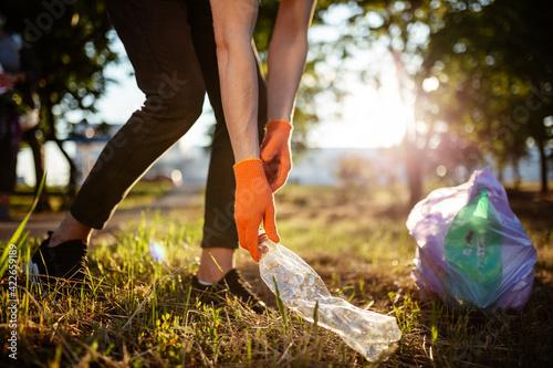 Obraz na płótnie Man picks up litter outdoors, collecting used plastic bottle trash