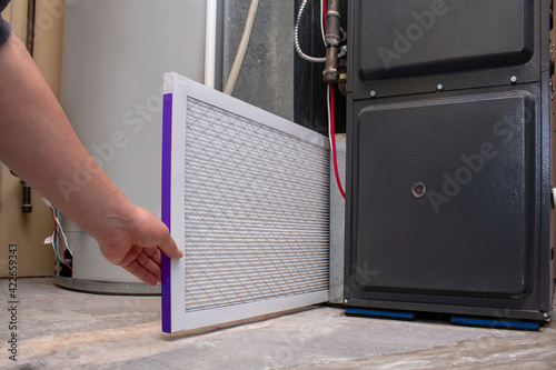 Photo A person changing an clean air filter on a high efficiency furnace