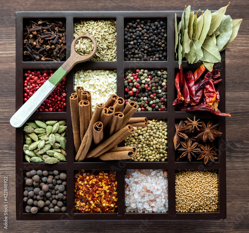 Fotografia Top down view of a variety of whole spices in a compartment box with a wooden spoon of fennel seeds on top