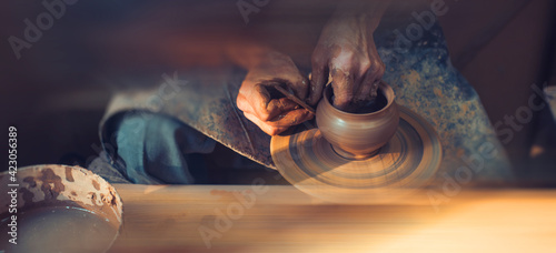 Fotografia, Obraz A male artisan in a pottery workshop makes a piece of clay behind a pottery wheel