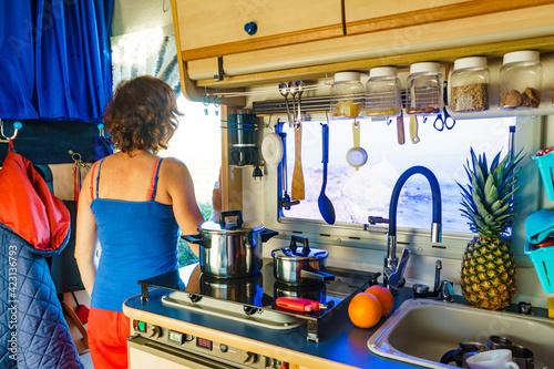 Woman inside Caravan, kitchen area Fotobehang