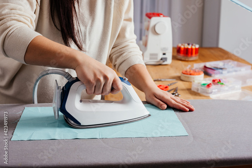 Obraz na plátne Process of ironing textile before cutting the pattern and sewing