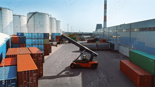 Fotografija Aerial Shot of a Container Handler Carrying a Large Red Shipping Cargo Container in a Shipyard Terminal