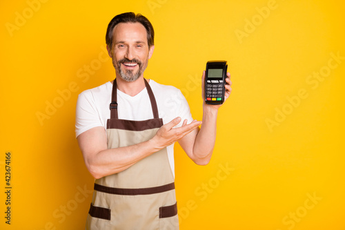 Fotografia Portrait of attractive cheerful guy store owner demonstrating safe pos terminal