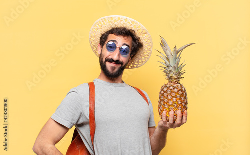 Fotografia young crazy traveler man happy expression and holding a pineapple