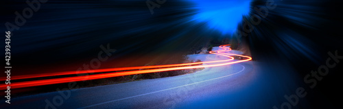 Valokuva Cars light trails at night in a curve mountains road, panorama