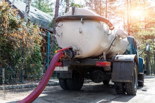 Obraz na płótnie Close-up pipe hose of sewage truck car engine emptying home sewerage tank
