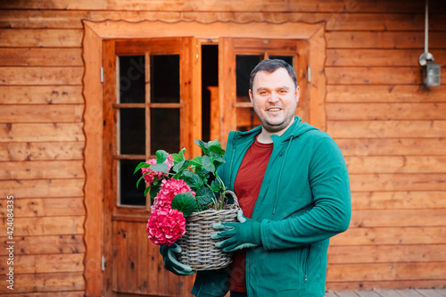Obraz na plátne A young horticulturist holds a red hydrangea and smiles
