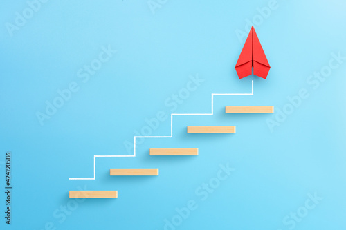 Fototapeta Wooden block stacking as step stair with red paper plane on blue background, Lad
