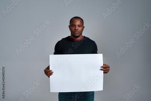 Valokuvatapetti Calm african american man holding blank placard mockup