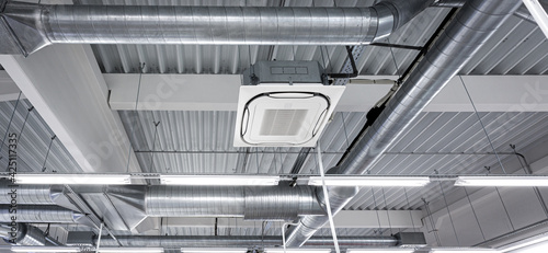 Fotografia Ceiling mounted cassette type air condition units with other parts of ventilation system (tubes, cables and vents) located inside commercial hall with hanging lights and other construction parts