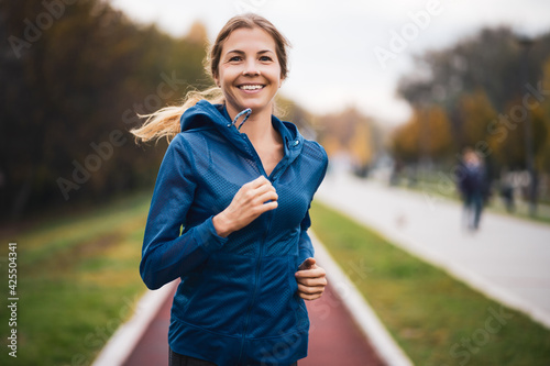 Canvas Print Beautiful adult woman is jogging outdoor on cloudy day in autumn.