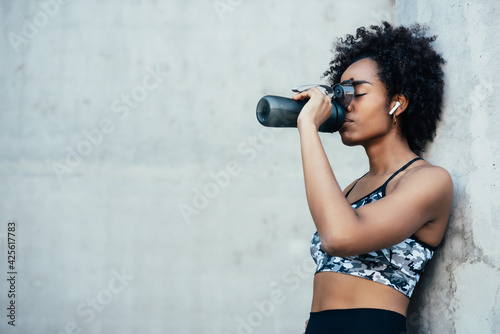 Fotomural Athletic woman drinking water after work out outdoors.