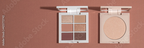 Eye shadow palette and highlighting powder on pink clean background with hard light Fototapeta
