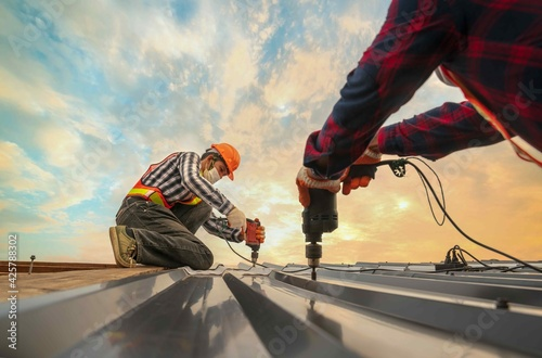 Roofer worker in protective uniform wear gloves, using electric screw drill installing iron roof or metal sheet on top of the new roof,Concept of residential building safty under construction.