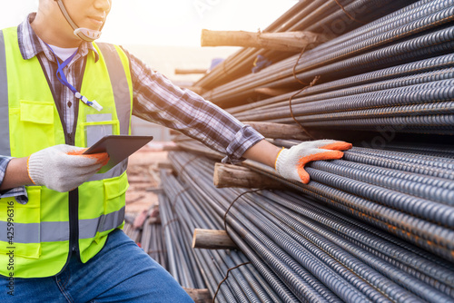 Close up of Construction engineer or worker use a tablet checking quality steel for concrete foundation and check the quality of round bar at construction site