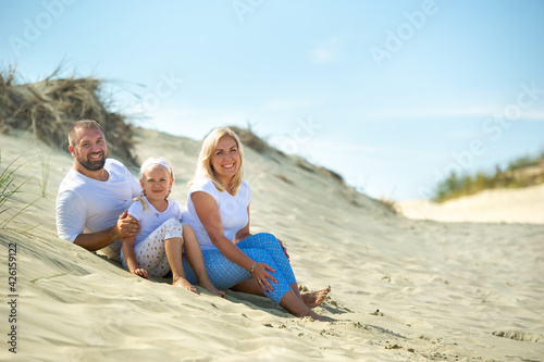 Obraz na plátne A family of three sit on the sand dunes near the town of Nida