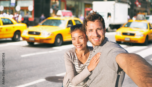 Fotografiet New York travel selfie tourists couple taking photo on NYC city street summer holiday vacation with yellow taxi cabs in the background