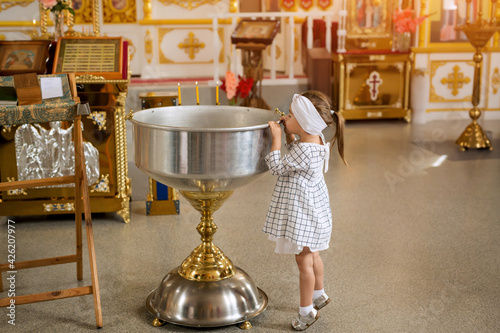 Slika na platnu A curious girl looks into the bowl for the sacrament of infant baptism in the Orthodox church