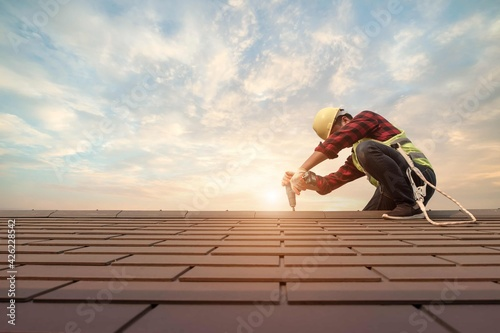 Fototapeta Roofer working in special protective work wear gloves, using air or pneumatic na