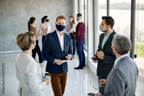Group of business people wearing face masks while talking hallway of an office building Fototapet
